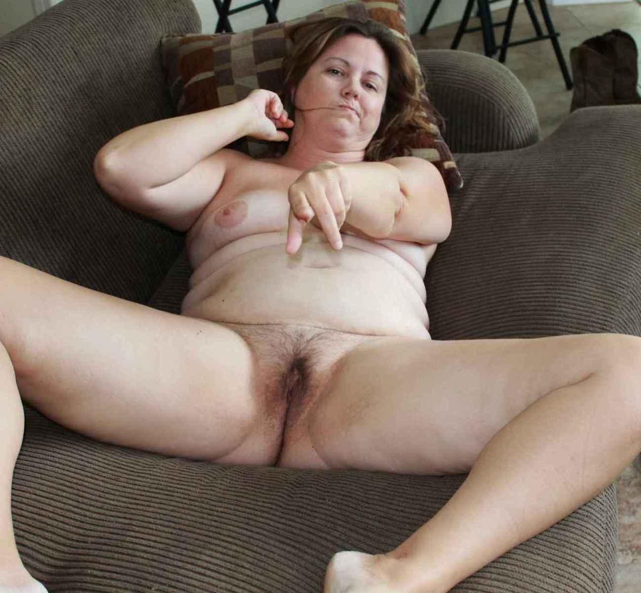 Grosse maman poilue écarte les cuisses sur le canapé