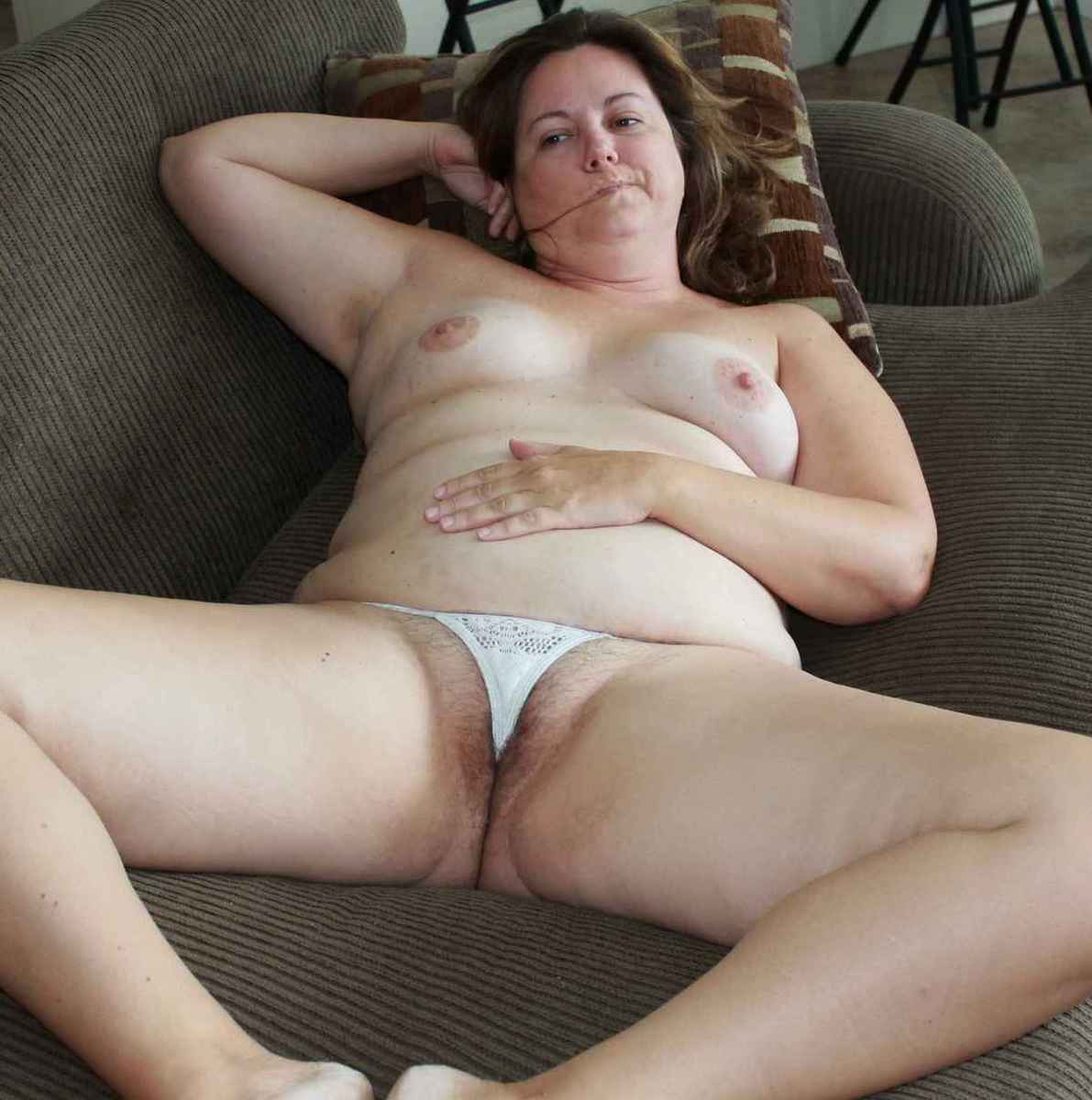 Grosse maman poilue écarte les cuisses sur le canapé ...