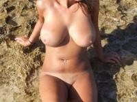 Jolie brunette aux gros seins finit nue sur la plage…