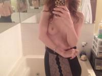 Brunette aux petits seins en mode selfies devant la glace