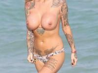 Mature blonde en bikini tatouée de partout exhibe ses gros seins siliconés !